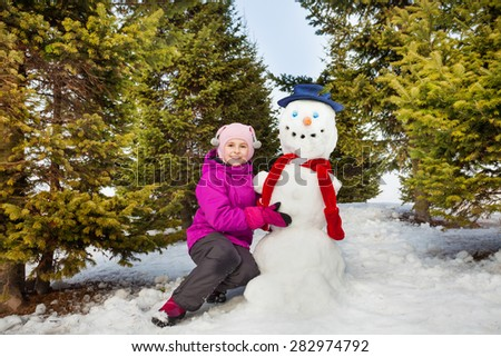 Beautiful little girl and snowman with red scarf - stock photo