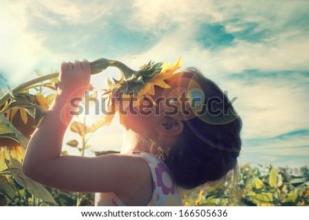 Beautiful little girl and sunflower - stock photo
