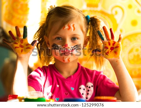 Beautiful little girl artist with paint of face