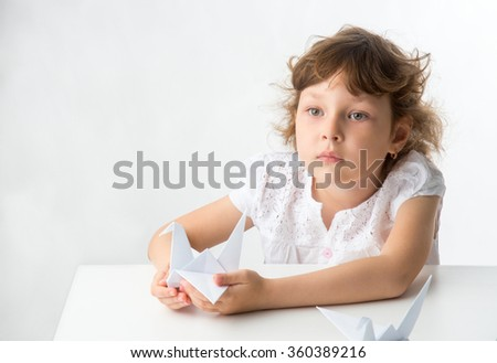 Beautiful little girl at the table  with paper cranes