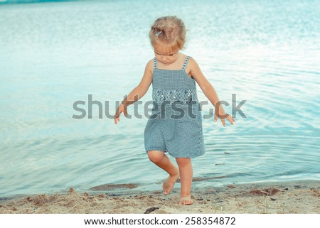 beautiful little girl child walking along the beach on a background of water - stock photo