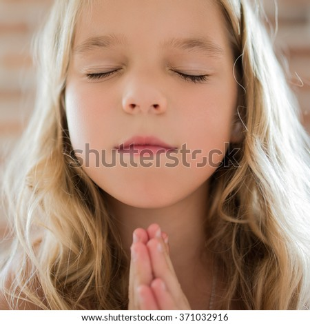 Beautiful little girl closed her eyes and prays on a brick wall background.