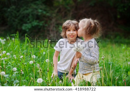 Beautiful little girl collects dandelions in the yard and kiss boy.