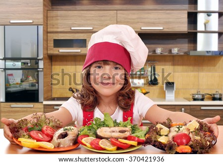 beautiful little girl cook with prepared salmon seafood in kitchen - stock photo