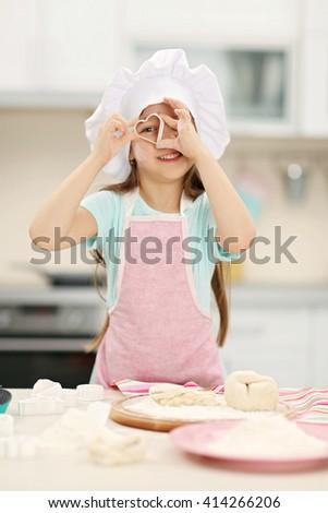 Beautiful little girl cutting hearts from a dough - stock photo
