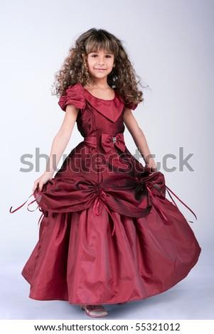 Beautiful little girl dancing in wine red dress - stock photo