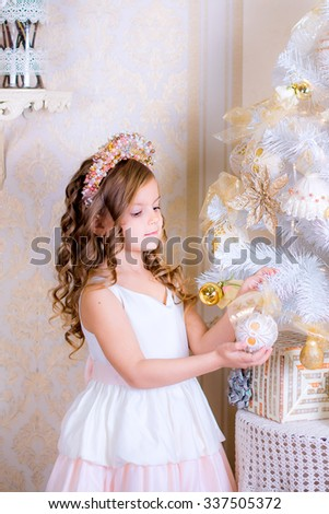 beautiful little girl decorate white Christmas tree golden balls