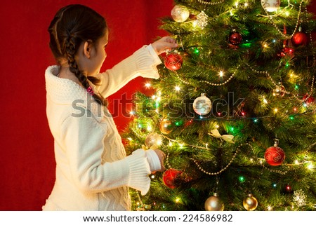 Beautiful little girl decorating Christmas tree - stock photo
