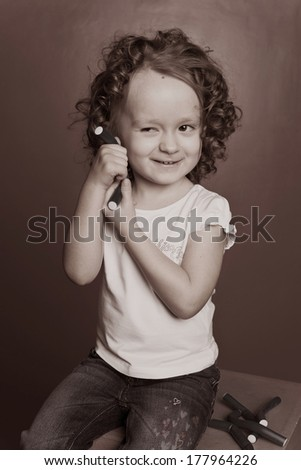 beautiful little girl doing her hair curly with hair curlers rollers black and white