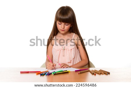 Beautiful little girl draws while sitting at a table on a white background - stock photo