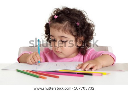 Beautiful little girl draws with colored pencils sitting at the table