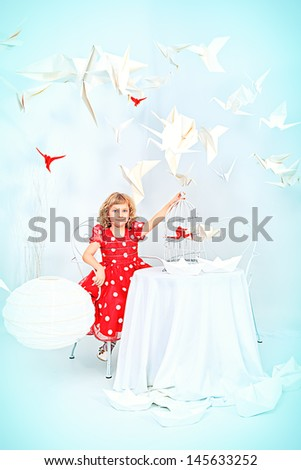 Beautiful little girl dreaming with her red paper bird in a birdcage. - stock photo