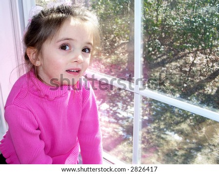 Beautiful little girl dressed in a hot pink shirt with brown hair and eyes sitting in a window. - stock photo