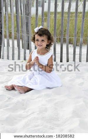Beautiful little girl dressed in white sitting on the sand with her hands in a prayer position. - stock photo
