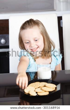 beautiful little girl drinking milk and cookies - stock photo