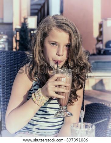 Beautiful Little girl drinking tasty milk cocktails at outdoor cafe on sunset - stock photo