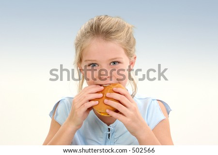 Beautiful Little Girl Eating a Cheeseburger over blue background.  Shot in studio.