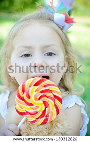 Beautiful little girl eating lollipop - stock photo