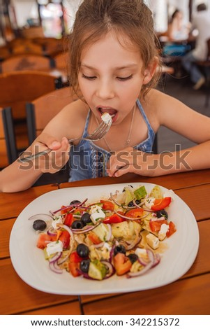 Beautiful little girl eats greek salad at the restaurant. - stock photo