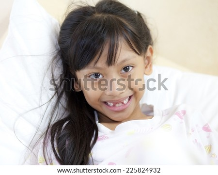 beautiful little girl grinning at the camera showing off her missing front tooth, close up portrait  - stock photo