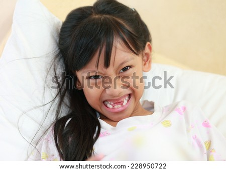 beautiful little girl grinning at the camera showing off her missing front tooth, close up portrait.  - stock photo