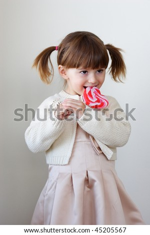 Beautiful little girl holding a big heart shaped lollipop - stock photo