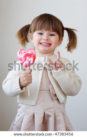 Beautiful little girl holding a big heart shaped lollipop - stock photo