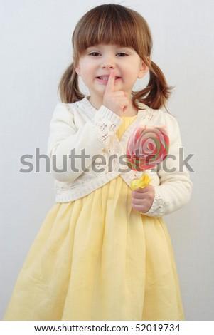 Beautiful little girl holding a big round swirl lollipop - stock photo