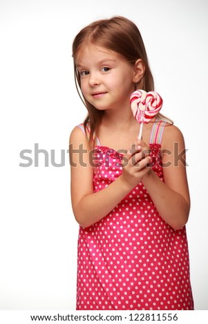 Beautiful little girl holding a big round swirl lollipop on Food and drink concept theme