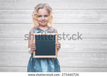 Beautiful little girl holding a board for chalk. Empty space for text. School lessons. Back to school. Wood backgrounds - stock photo