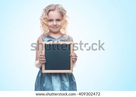 Beautiful little girl holding a board for chalk. Empty space for text. School lessons. Back to school. Colored backgrounds - stock photo
