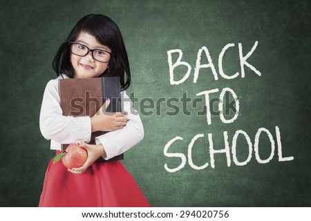 Beautiful little girl holding a book and apple back to school - stock photo