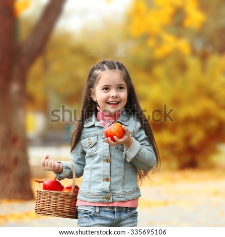 Beautiful little girl holding basket of apples, outdoor - stock photo