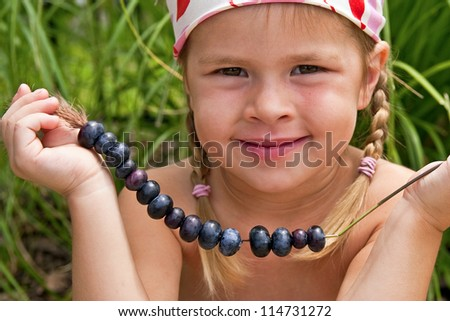 Beautiful little girl holding freshly picked blueberries on straw