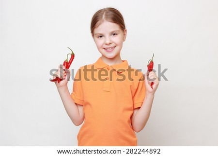 Beautiful little girl holding red hot chillies - stock photo