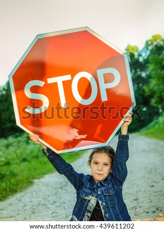 "Beautiful little girl holding red sign ""STOP"". - stock photo"
