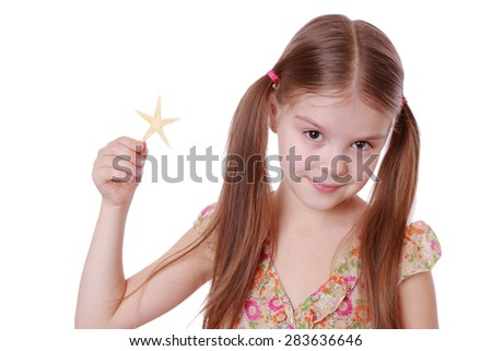Beautiful little girl holds a large star fish, isolated on white - stock photo