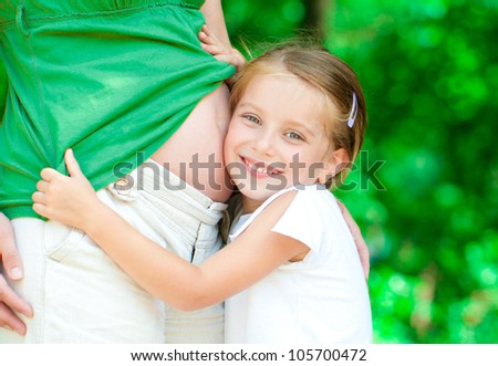 Beautiful little girl hugging a pregnant mother's belly