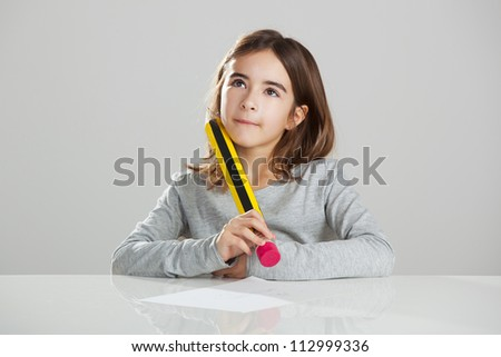 Beautiful little girl in a desk playing with a big pencil, against a gray background - stock photo