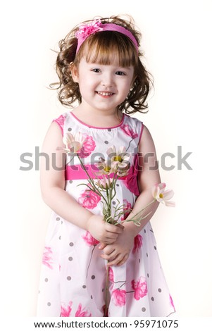 beautiful little girl in a dress with a flower in your hand - stock photo