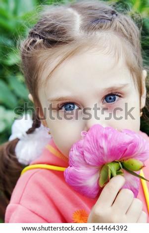 Beautiful Little Girl in a Garden Sniffs Flower - stock photo