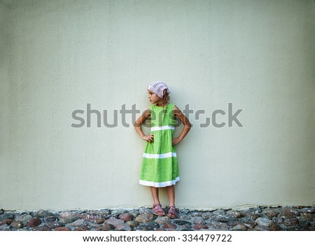 Beautiful little girl in a green dress on a background of a large stucco wall. - stock photo