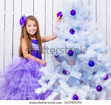 beautiful little girl in a lilac dress decorated white Christmas tree - stock photo