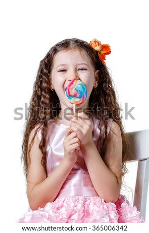 beautiful little girl in a pink dress eating a lollipop on a white background - stock photo