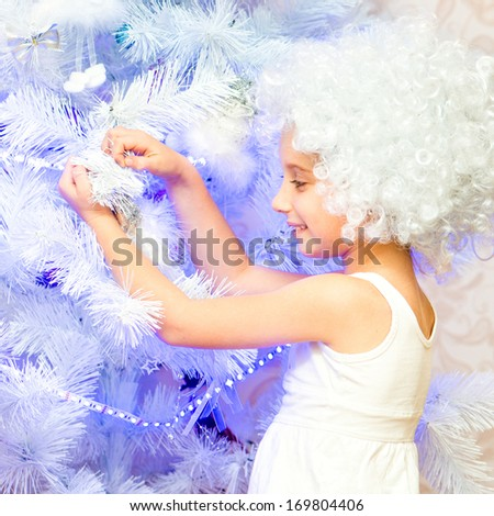 beautiful little girl in a white wig decorated Christmas tree - stock photo