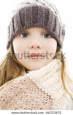 Beautiful little girl in cap and scarf. Isolated on white.