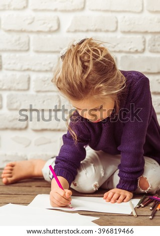 Beautiful little girl in casual clothes is drawing using colorful pencils, sitting against white brick wall - stock photo