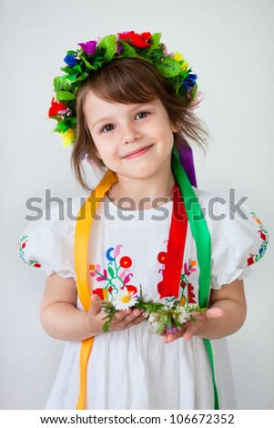 Beautiful little girl in ethnic dress with flower wreath