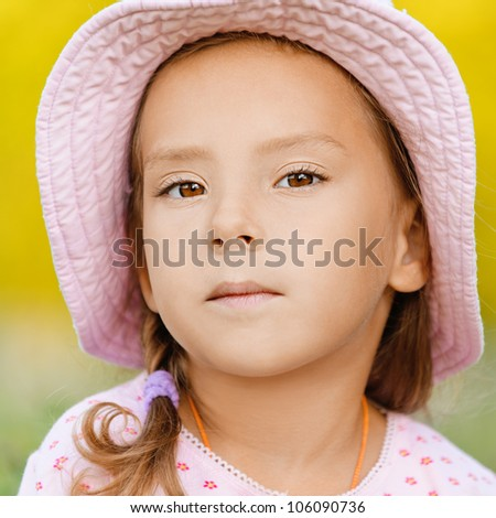 Beautiful little girl in hat close up, against summer green of park.