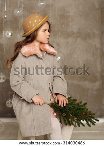Beautiful little girl in hat. New Year and Christmas Tree Holiday  - stock photo